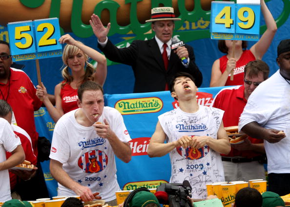 NEW YORK - JULY 4:  Joey Chestnut of San Jose, California (C) and Takeru Kobayashi of Nagano, Japan (R) stuff hot dogs into their mouths during Nathan's Famous Fourth of July hot dog eating contest on July 4, 2009 in Coney Island in the Brooklyn borough of New York City.  Chestnut defeated Kobayashi with eating 68 to his 64.5 hotdogs. Kobayashi won six previous competitions before tying last year with Chestnut. (Photo by Yana Paskova/Getty Images)