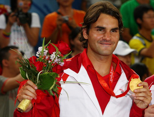 BEIJING - AUGUST 16:  Roger Federer of Switzerland celebrates with his gold medal won with partner Stanislas Wawrinka after defeating Thomas Johansson and Simon Aspelin of Sweden during the men's doubles gold medal tennis match at the Olympic Green Tennis Center on Day 8 of the Beijing 2008 Olympic Games on August 16, 2008 in Beijing, China.  (Photo by Clive Brunskill/Getty Images)