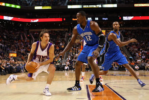 PHOENIX - DECEMBER 11:  Steve Nash #13 of the Phoenix Suns handles the ball under pessure from Dwight Howard #12 of the Orlando Magic during the NBA game at US Airways Center on December 11, 2009 in Phoenix, Arizona. The Suns defeated the Magic 106-103.  NOTE TO USER: User expressly acknowledges and agrees that, by downloading and or using this photograph, User is consenting to the terms and conditions of the Getty Images License Agreement.  (Photo by Christian Petersen/Getty Images)