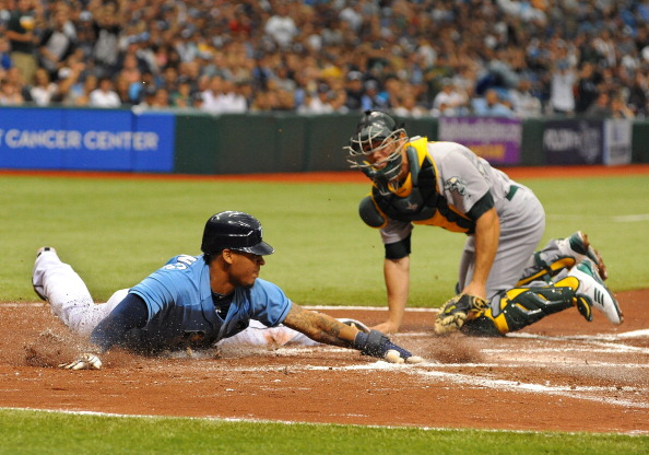 ST. PETERSBURG, FL - MAY 6: Outfielder Desmond Jennings #8 of the Tampa Bay Rays slides into home plate for a run against the Oakland Athletics May 6, 2012 at Tropicana Field in St. Petersburg, Florida. The Rays scored 4 runs on 2 hits in the inning. (Photo by Al Messerschmidt/Getty Images)
