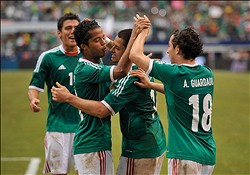 Jun 3, 2012; Arlington, TX, USA; Mexico forward Giovani dos Santos (10) and forward Javier Chicharito Hernandez (14) and midfielder Andres Guardado (18) celebrate a goal against Brazil during the first half at Cowboys Stadium. Mexico shut out Brazil 2-0. Mandatory Credit: Jerome Miron-US PRESSWIRE