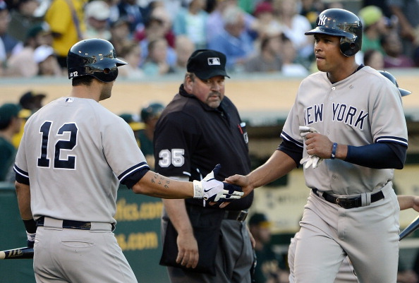 OAKLAND, CA - JULY 21:  Alex Rodriguez #13 of the New York Yankees is congratulated by Eric Chavez #12 after Rodriguez scored in the fourth inning against the Oakland Athletics at O.co Coliseum on July 21, 2012 in Oakland, California.  (Photo by Thearon W. Henderson/Getty Images)