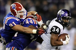 December 21, 2011; San Diego, CA, USA; TCU Horned Frogs running back Ed Wesley (34) fights for extra yardage while being chased by Louisiana Tech Bulldogs defensive end Matt Broha (91) and linebacker Adrien Cole (44) during the second quarter in the Poinsettia Bowl at Qualcomm Stadium.  Mandatory Credit: Christopher Hanewinckel-US PRESSWIRE