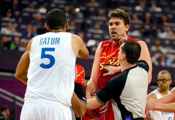 LONDON, ENGLAND - AUGUST 08:  Marc Gasol #13 of Spain is held back by a referee as he runs towards Nicolas Batum #5 of France after Batum fouled Juan-Carlos Navarro #7 late in the fourth quarter during the Men's Basketball quaterfinal game on Day 12 of the London 2012 Olympic Games at North Greenwich Arena on August 8, 2012 in London, England.  (Photo by Ronald Martinez/Getty Images)
