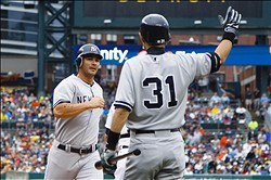 August 9, 2012; Detroit, MI, USA; New York Yankees third baseman Eric Chavez (12) receives congratulations from right fielder Ichiro Suzuki (31) after scoring during the second inning against the Detroit Tigers at Comerica Park. Mandatory Credit: Rick Osentoski-US PRESSWIRE