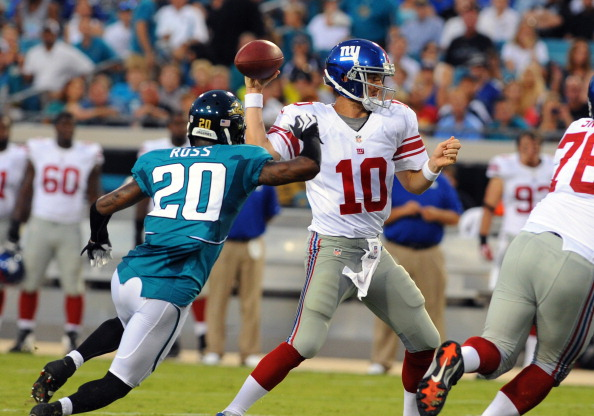 JACKSONVILLE, FL - AUGUST 10:  Cornerbac Aaron Ross #20 of the Jacksonville Jaguars rushes quarterback Eli Manning #10 of the New York Giants during a pre-season football game August 10, 2011 at EverBank Field in Jacksonville, Florida. Ross was penalized for a helmet hit on the play. (Photo by Al Messerschmidt/Getty Images)