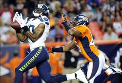 Aug 18, 2012; Denver, CO, USA;  Seattle Seahawks wide receiver Terrell Owens (10) drops a pass as Denver Broncos cornerback Chris Harris (25) defends in the second quarter against the Seattle Seahawks at Sports Authority Field.  Mandatory Credit: Byron Hetzler-US PRESSWIRE