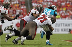 September 9, 2012; Tampa, FL, USA; Tampa Bay Buccaneers defensive tackle Roy Miller (90) and defensive end Michael Bennett (71) tackle Carolina Panthers running back DeAngelo Williams (34) in the second half at Raymond James Stadium. Tampa Bay Buccaneers defeated the Carolina Panthers 16-10. Mandatory Credit: Kim Klement-US PRESSWIRE