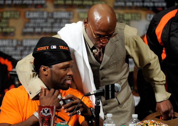 LAS VEGAS, NV - SEPTEMBER 17:  Rapper 50 Cent sits at the table as he is hugged by Floyd Mayweather Jr. during the post-fight news conference after Mayweather Jr. knocks out Victor Ortiz in the WBC welterweight title fight at the MGM Grand Garden Arena on September 17, 2011 in Las Vegas, Nevada.  (Photo by Ethan Miller/Getty Images)