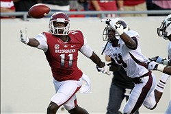 Sep 8, 2012; Little Rock, AR, USA; Arkansas Razorbacks wide receiver Cobi Hamilton (11) reaches for a pass as Louisiana Monroe Warhawks cornerback Otis Peterson (9) is called for pass interference during the second quarter at War Memorial Stadium. Mandatory Credit: Nelson Chenault-US PRESSWIRE