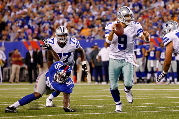 EAST RUTHERFORD, NJ - SEPTEMBER 05:  Quarterback Tony Romo #9 of the Dallas Cowboys runs with the ball on his way to throwing a touchdown to wide receiver Kevin Ogletree #85 in the second quarter as he his chased by defensive end Jason Pierre-Paul #90 of the New York Giants during the 2012 NFL season opener at MetLife Stadium on September 5, 2012 in East Rutherford, New Jersey.  (Photo by Jeff Zelevansky/Getty Images)