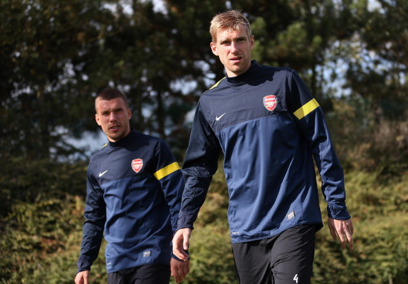 ST ALBANS, ENGLAND - SEPTEMBER 17:  Per Mertesacker of Arsenal (R) and Lukas Podolski of Arsenal arrive during a training session at London Colney on September 17, 2012 in St Albans, England. (Photo by Julian Finney/Getty Images)