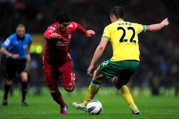 NORWICH, ENGLAND - APRIL 28:  Luis Suarez of Liverpool goes past Elliott Ward of Norwich during the Barclays Premier League match between Norwich City and Liverpool at Carrow Road on April 28, 2012 in Norwich, England.  (Photo by Jamie McDonald/Getty Images)