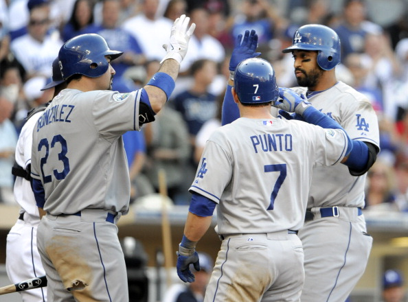 SAN DIEGO, CA - SEPTEMBER 26:  Matt Kemp #27 of the Los Angeles Dodgers, right, is congratulated by Adrian Gonzalez #23, left, and Nick Punto #7, center, after he hit a two-run homer during the sixth inning of a baseball game against the San Diego Padres at Petco Park on September 26, 2012 in San Diego, California.  (Photo by Denis Poroy/Getty Images)
