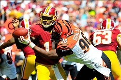 September 23, 2012; Landover, MD, USA; Washington Redskins quarterback Robert Griffin III (10) fumbles after being hit by Cincinnati Bengals defensive end Carlos Dunlap (96) during the second quarter at FedEx Field. Mandatory Credit: Dale Zanine-US PRESSWIRE