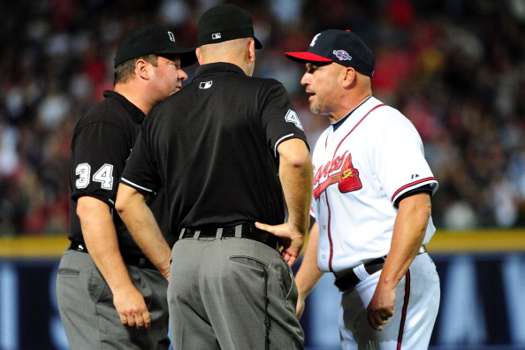 ATLANTA, GA - OCTOBER 05:  Manager Fredi Gonzalez #33 of the Atlanta Braves argues an infield fly ruling in the eighth inning with third base umpire Jeff Nelson and left field umpire Sam Holbrook while taking on the St. Louis Cardinals during the National League Wild Card playoff game at Turner Field on October 5, 2012 in Atlanta, Georgia.  (Photo by Scott Cunningham/Getty Images)