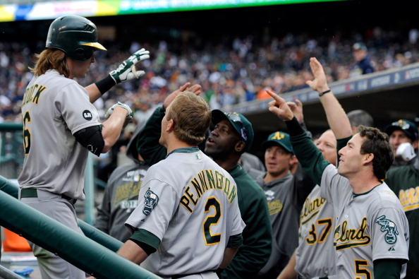 DETROIT, MI - OCTOBER 07:  Josh Reddick (L) #16 of the Oakland Athletics celebrates with teammates in the dugout after Reddick scored on his solo home run in the top of th eighth inning against the Detroit Tigers during Game Two of the American League Division Series at Comerica Park on October 7, 2012 in Detroit, Michigan.  (Photo by Jason Miller/Getty Images)