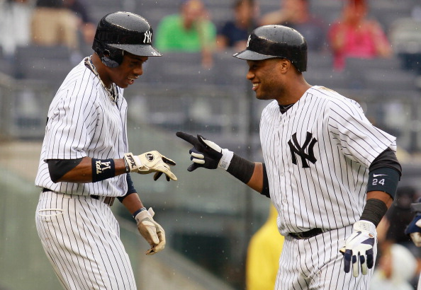 NEW YORK, NY - AUGUST 01:  Robinson Cano #24 of the New York Yankees is greeted by Curtis Granderson #14 after connecting on a fourth-inning grand slam against the Baltimore Orioles at Yankee Stadium on August 1, 2012 in the Bronx borough of New York City.  (Photo by Mike Stobe/Getty Images)