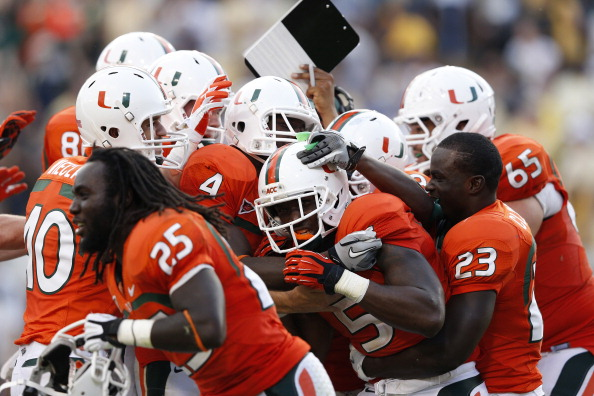 ATLANTA, GA - SEPTEMBER 22: Mike James #5 of the Miami Hurricanes gets mobbed by teammates after rushing for a 25-yard touchdown in overtime to win the game against the Georgia Tech Yellow Jackets at Bobby Dodd Stadium on September 22, 2012 in Atlanta, Georgia. Miami won 42-36. (Photo by Joe Robbins/Getty Images)