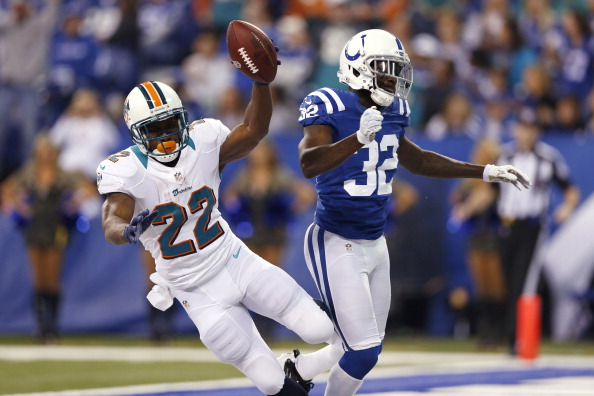 INDIANAPOLIS, IN - NOVEMBER 04: Reggie Bush #22 of the Miami Dolphins gets bumped late after an 18-yard touchdown run by Cassius Vaughn #32 of the Indianapolis Colts during the game at Lucas Oil Stadium on November 4, 2012 in Indianapolis, Indiana. (Photo by Joe Robbins/Getty Images)