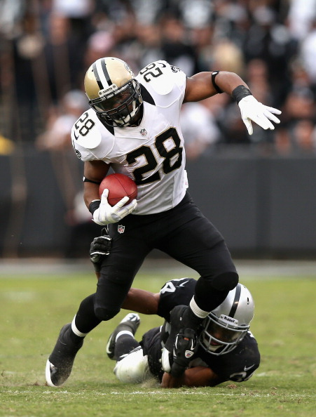 OAKLAND, CA - NOVEMBER 18:  Mark Ingram #28 of the New Orleans Saints tries to break away from Mike Mitchell #34 of the Oakland Raiders at O.co Coliseum on November 18, 2012 in Oakland, California.  (Photo by Ezra Shaw/Getty Images)