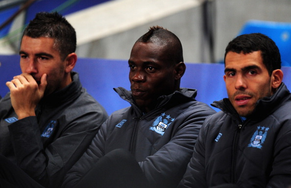 MANCHESTER, ENGLAND - OCTOBER 03:  Mario Balotelli of Manchester City watches from the bench with Aleksandar Kolarov (L) and Carlos Tevez (R) during the UEFA Champions League Group D match between Manchester City and Borussia Dortmund at the Etihad Stadium on October 3, 2012 in Manchester, England.  (Photo by Stu Forster/Getty Images)