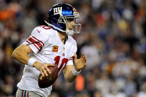LANDOVER, MD - DECEMBER 03:  Quarterback Eli Manning #10 of the New York Giants runs five-yards for a first down in the third quarter against the Washington Redskins at FedExField on December 3, 2012 in Landover, Maryland.  (Photo by Patrick McDermott/Getty Images)