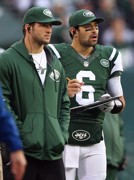 EAST RUTHERFORD, NJ - DECEMBER 02:  Mark Sanchez #6 of the New York Jets works the clipboard as teammate Tim Tebow #15 stands by in the third quarter against the Arizona Cardinals  on December 2, 2012 at MetLife Stadium in East Rutherford, New Jersey. The New York Jets defeated the Arizona Cardinals 7-6.  (Photo by Elsa/Getty Images)