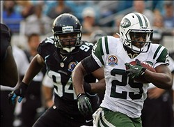 Dec 9, 2012; Jacksonville FL, USA; New York Jets running back Bilal Powell (29) moves past Jacksonville Jaguars defensive lineman Jeremy Mincey (94) in the fourth quarter of their game at EverBank Field. The New York Jets beat the Jacksonville Jaguars 17-10. Mandatory Credit: Phil Sears-USA TODAY Sports