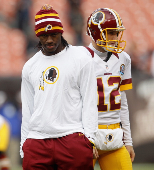 CLEVELAND, OH - DECEMBER 16:  Quarterback Robert Griffin III #10 of the Washington Redskins walks by quarterback Kirk Cousins #12 against the Cleveland Browns at Cleveland Browns Stadium on December 16, 2012 in Cleveland, Ohio.  (Photo by Matt Sullivan/Getty Images)