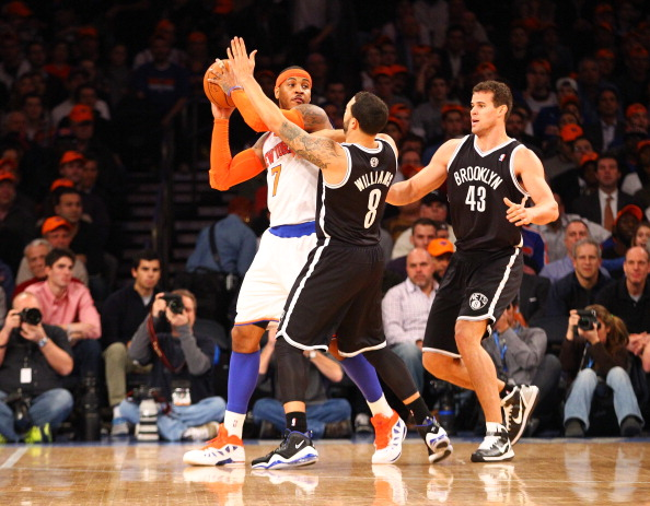 NEW YORK, NY - DECEMBER 19:  Carmelo Anthony #7 of the New York Knicks is double teamed by Deron Williams #8, and Kris Humphries #43 of the Brooklyn Nets during their game at Madison Square Garden on December 19, 2012 in New York City.  NOTE TO USER: User expressly acknowledges and agrees that, by downloading and or using this photograph, User is consenting to the terms and conditions of the Getty Images License Agreement.  (Photo by Al Bello/Getty Images)