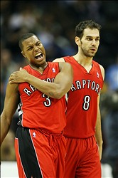 December 3, 2012; Denver, CO, USA; Toronto Raptors guard Kyle Lowry (3) reacts after injuring his shoulder as he and guard Jose Calderon (8) walk back to the bench during a timeout during the second half against the Denver Nuggets at the Pepsi Center.  The Nuggets won 113-110.  Mandatory Credit: Chris Humphreys-USA TODAY Sports