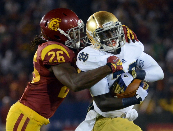 LOS ANGELES, CA - NOVEMBER 24:  Cierre Wood #20 of the Notre Dame Fighting Irish protects the ball as he is tackled by Josh Shaw #26 of the USC Trojans during a 22-13 Notre Dame win at Los Angeles Memorial Coliseum on November 24, 2012 in Los Angeles, California.  (Photo by Harry How/Getty Images)