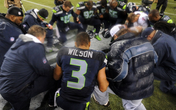 SEATTLE, WA. - DECEMBER 23: Quarterback Russell Wilson #3 of the Seattle Seahawks prays with a group after the game against the San Francisco 49ers at CenturyLink Field on December 23, 2012 in Seattle,Wa. The Seahawks won the game 42-13. (Photo by Steve Dykes/Getty Images)