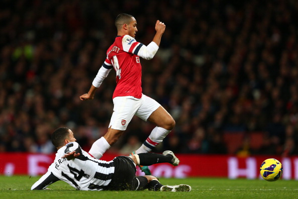 LONDON, ENGLAND - DECEMBER 29: James Perch of Newcastle United tackles Theo Walcott of Arsenal  during the Barclays Premier League match between Arsenal and Newcastle United at the Emirates Stadium on December 29, 2012 in London, England.  (Photo by Clive Mason/Getty Images)