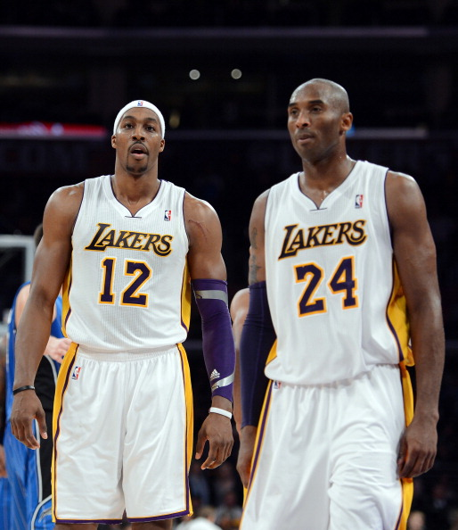 LOS ANGELES, CA - DECEMBER 02:  Dwight Howard #12 and Kobe Bryant #24 of the Los Angeles Lakers leave the court during a 113-103 Orlando Magic win at Staples Center on December 2, 2012 in Los Angeles, California.  NOTE TO USER: User expressly acknowledges and agrees that, by downloading and or using this photograph, User is consenting to the terms and conditions of the Getty Images License Agreement.  (Photo by Harry How/Getty Images)