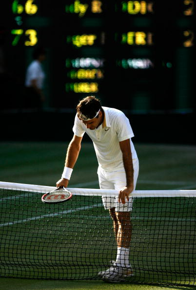 WIMBLEDON, ENGLAND - JULY 05:  Roger Federer of Switzerland rests on the net as he is victorious during the men's singles final match against Andy Roddick of USA on Day Thirteen of the Wimbledon Lawn Tennis Championships at the All England Lawn Tennis and Croquet Club on July 5, 2009 in London, England. Federer won 5-7, 7-6, 7-6, 3-6, 16-14.  (Photo by Paul Gilham/Getty Images)