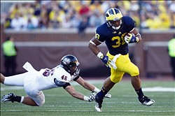 September 15, 2012; Ann Arbor, MI, USA; Michigan Wolverines running back Thomas Rawls (38) runs the ball past Massachusetts Minutemen defensive back Joe Colton (46) during the third quarter at Michigan Stadium. Michigan won 63-13. Mandatory Credit: Rick Osentoski-USA TODAY Sports