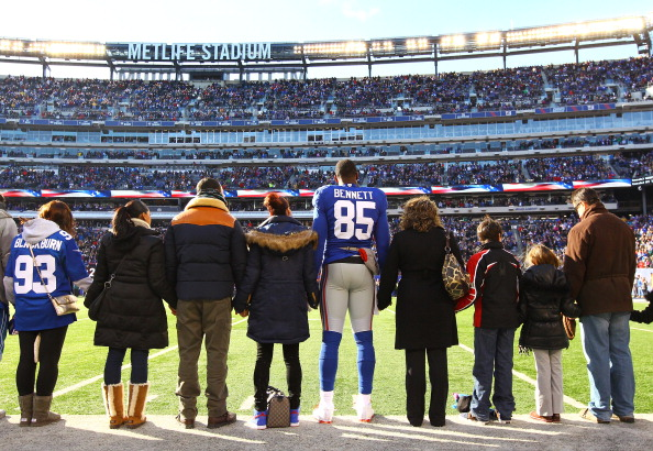 EAST RUTHERFORD, NJ - DECEMBER 30:   Martellus Bennett #85 of the New York Giants stands with  families of Sandy Hook Elementary School before the game against the Philadelphia Eagles  their game against the at MetLife Stadium on December 30, 2012 in East Rutherford, New Jersey.  (Photo by Al Bello/Getty Images)