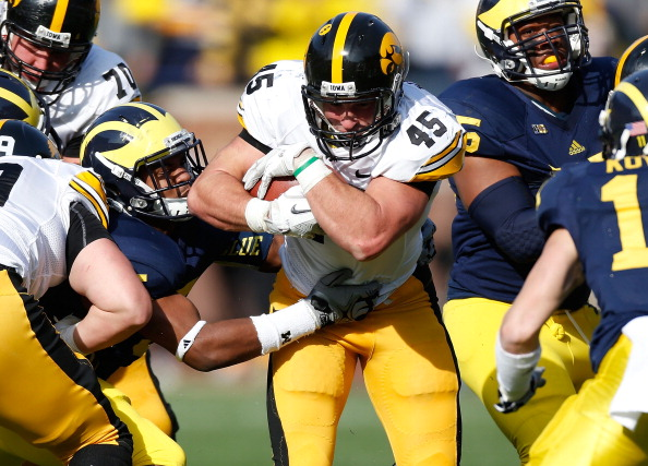 ANN ARBOR, MI - NOVEMBER 17:  Mark Weisman #45 of the Iowa Hawkeyes tries to split the tackles of Jibreel Black #55 and Courtney Avery #5 of the Michigan Wolverines at Michigan Stadium on November 17, 2012 in Ann Arbor, Michigan. (Photo by Gregory Shamus/Getty Images)