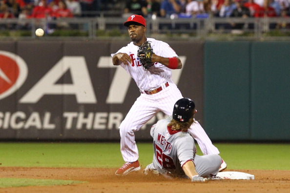 PHILADELPHIA - SEPTEMBER 26: Jimmy Rollins #11 of the Philadelphia Phillies throws to first base as Jayson Werth #28 slides into second during a game against the Washington Nationals at Citizens Bank Park on September 26, 2012 in Philadelphia, Pennsylvania. (Photo by Hunter Martin/Getty Images)