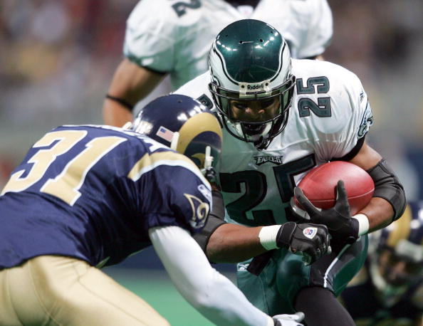 ST.LOUIS - DECEMBER 27:  Dorsey Levens #25 of the Philadelphia Eagles is stopped by Adam Archuleta #31 of the St. Louis Rams on December 27, 2004 at the Edward Jones Dome in St. Louis, Missouri.  (Photo by Elsa/Getty Images)