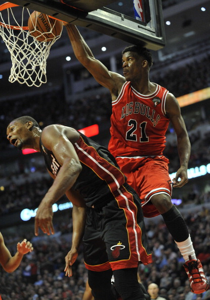 CHICAGO, IL - MARCH 27: Jimmy Butler #21 of the Chicago Bulls dunks over Chris Bosh #1 of the Miami Heat on March 27, 2013 at the United Center in Chicago, Illinois. The Chicago Bulls defeated  the Miami Heat 101 -97. NOTE TO USER: User expressly acknowledges and agrees that, by downloading and or using this photograph, User is consenting to the terms and conditions of the Getty Images License Agreement. (Photo by David Banks/Getty Images)