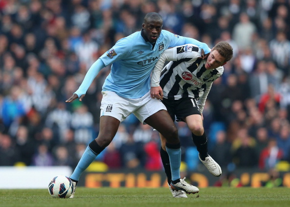 MANCHESTER, ENGLAND - MARCH 30:  Yaya Toure of Manchester City tussles for posession with Dan Gosling of Newcastle United during the Barclays Premier League match between Manchester City and Newcastle United at the Etihad Stadium on March 30, 2013 in Manchester, England.  (Photo by Alex Livesey/Getty Images)
