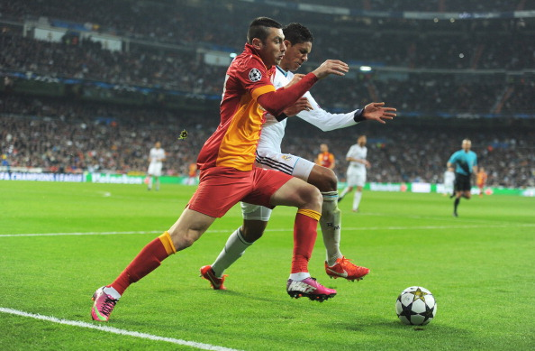 MADRID, SPAIN - APRIL 03:  Burak Yilmaz of Galatasaray takes on Raphael Varane of Real Madrid during the UEFA Champions League Quarter Final first leg match between Real Madrid and Galatasaray at Estadio Santiago Bernabeu on April 3, 2013 in Madrid, Spain.  (Photo by Gonzalo Arroyo Moreno/Getty Images)