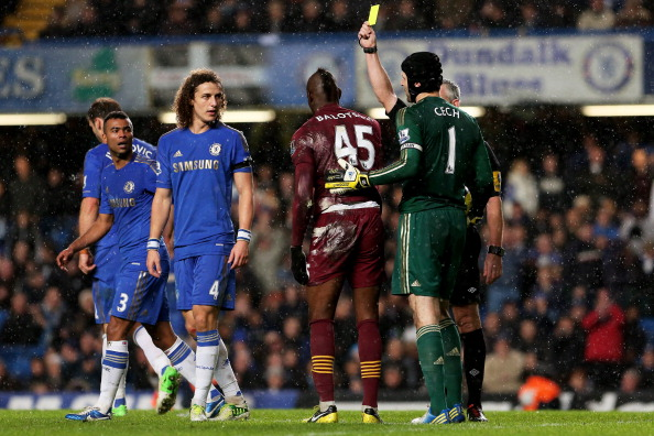 LONDON, ENGLAND - NOVEMBER 25: Substitute Mario Balotelli of Manchester City is shown the yellow card for diving by Referee Chris Foy during the Barclays Premier League match between Chelsea and Manchester City at Stamford Bridge on November 25, 2012 in London, England.  (Photo by Julian Finney/Getty Images)
