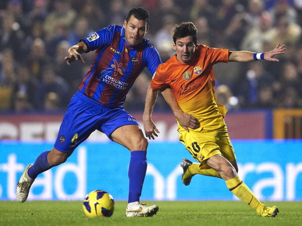 VALENCIA, SPAIN - NOVEMBER 25:  David Navarro (L) of Levante competes for the ball with Lionel Messi of Barcelona during the la Liga match between Levante UD and FC Barcelona at Ciutat de Valencia on November 25, 2012 in Valencia, Spain.  (Photo by Manuel Queimadelos Alonso/Getty Images)