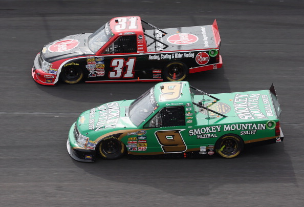 ROCKINGHAM, NC - APRIL 14:  James Buescher, driver of the #31 Rheem Chevrolet, races against Ron Hornaday Jr, driver of the #9 Smokey Mountain Herbal Snuff Chevrolet, during the NASCAR Camping World Truck Series Carolina 200 at Rockingham Speedway on April 14, 2013 in Rockingham, North Carolina.  (Photo by Streeter Lecka/Getty Images)