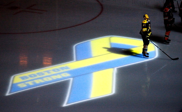 BOSTON, MA - APRIL 17:  Dennis Seidenberg #44 of the Boston Bruins stands near aa projection of the Boston Marathon Memorial Ribbon seen on the ice during pre game ceremonies in remembrance of the Boston Marathon bombing victims before a game between the Buffalo Sabres and the Boston Bruins at TD Garden on April 17, 2013 in Boston, Massachusetts.  (Photo by Jim Rogash/Getty Images)
