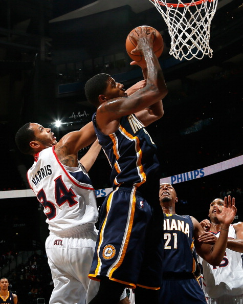 ATLANTA, GA - NOVEMBER 07:  Paul George #24 of the Indiana Pacers grabs a rebound against Devin Harris #34 of the Atlanta Hawks at Philips Arena on November 7, 2012 in Atlanta, Georgia.  NOTE TO USER: User expressly acknowledges and agrees that, by downloading and or using this photograph, User is consenting to the terms and conditions of the Getty Images License Agreement.  (Photo by Kevin C. Cox/Getty Images)